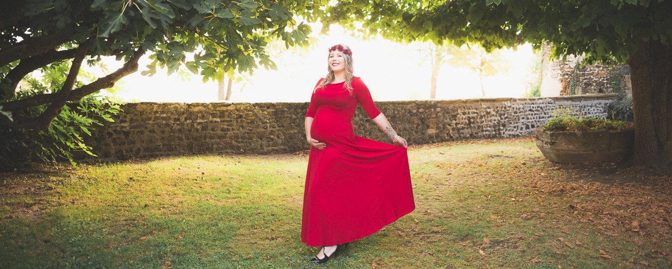Robe de grossesse rouge dans un parc
